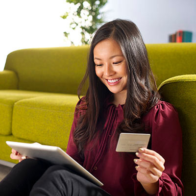 Woman sittting on carpet leaning against a couch while using a tablet and holding a client bank account card