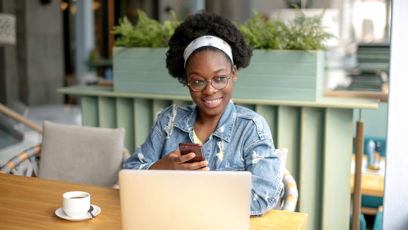 A young girl smiling and sitting by a coffee table with her phone and laptop
